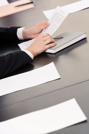 Image of human hands holding pen and documents with notebook, papers near by on the table Stock Photo - 3415032