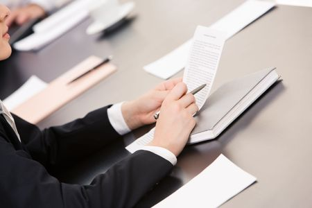 Close-up of businesswoman holding document and reading it at workplace Stock Photo - 3419433