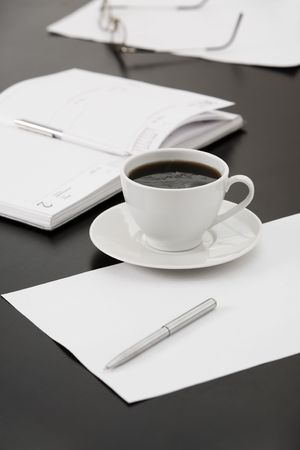 Morning workplace: cup of coffee, papers, notebook, pens, glasses on the table Stock Photo - 3419435