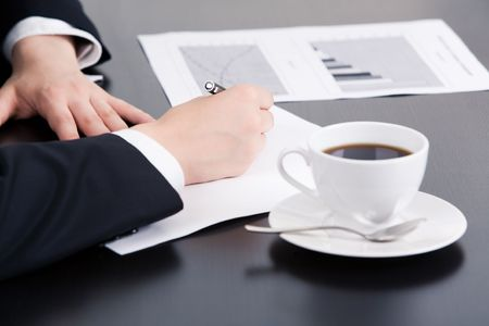 Close-up of businesswoman's hand writing something on paper with cup of coffee and document near by Stock Photo - 3419436