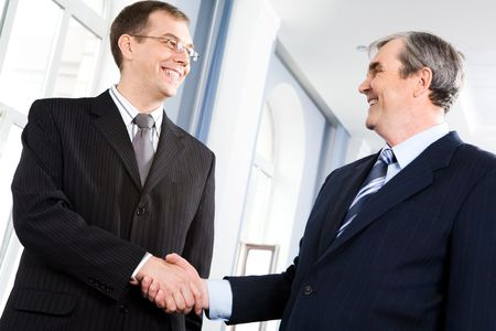 shake hands: Portrait of businessmen shaking hands greeting each other in the corridor