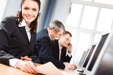 Successful woman wearing headset looking at camera on background of working men Stock Photo - 3421155