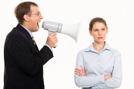 Portrait of angry boss shouting at his secretary through megaphone who is indifferent to it photo
