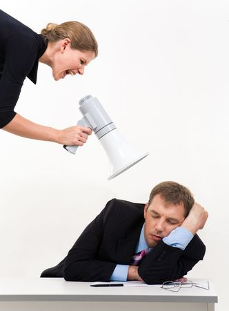 him: Portrait of businessman sleeping at workplace with businesswoman over him waking him up Stock Photo