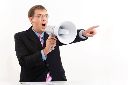 aside: Portrait of unhappy man in suit speaking through megaphone and pointing aside Stock Photo