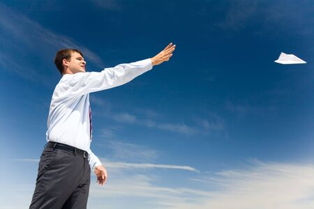 Portrait of handsome man launching paper aircraft into blue sky at summer photo