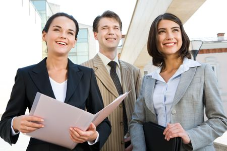 Portrait of business team outside looking straight and slightly upwards with smiles photo