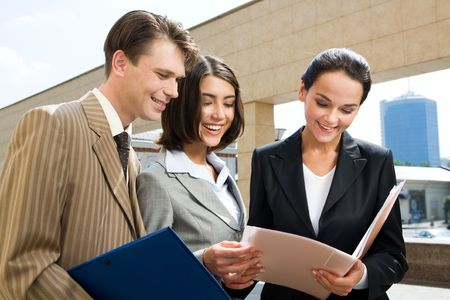 Photo of happy businesspeople communicating with each other while looking through documents Stock Photo - 3421184