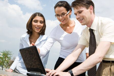 Image of three business partners looking at laptop monitor while man typing on it photo