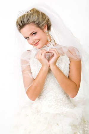 Portrait of bride wearing snow-white beautiful dress and making shape of heart with her hands while looking at camera photo