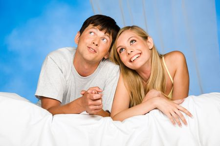 Portrait of happy couple lying in the bed looking upward  photo