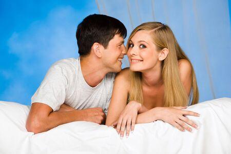 enamorados en la cama: Imagen del hombre que habla algo de la mujer en los o�dos  Foto de archivo