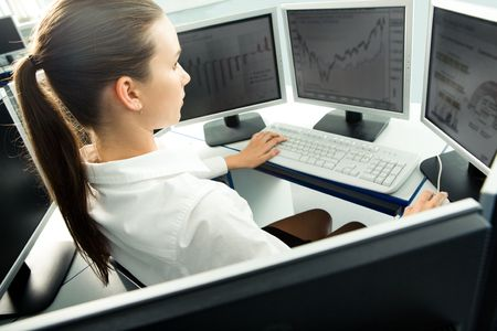 computer worker: Aside view of student sitting at computer with serious expression and looking at monitor of computer Stock Photo