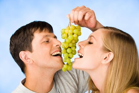 Portrait of man and young woman eating bunch of grapes  photo