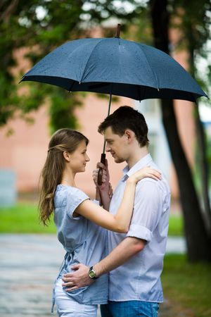 Portrait of couple in love standing outside under umbrella and looking at each other Stock Photo - 3452416