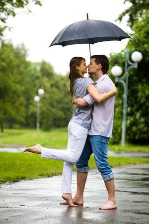 women kissing: Photo of romantic barefooted couple standing on the road in rain and going to kiss each other
