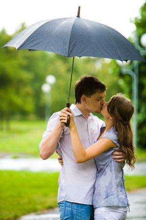 sotto la pioggia: Ritratto di giovane romantico che abbraccia e bacia a vicenda durante ombrello sotto la pioggia