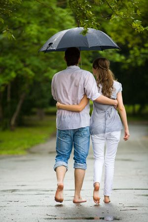 couple in rain: Rear backs of couple embracing each other in the park   Stock Photo