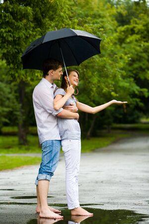 Portrait of man hugging happy woman under umbrella