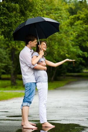 amorous woman: Portrait of man hugging happy woman under umbrella