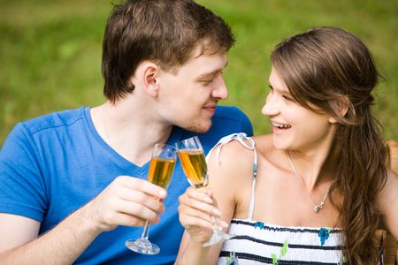 Photo of two happy people drinking wine and looking at each other with smiles photo