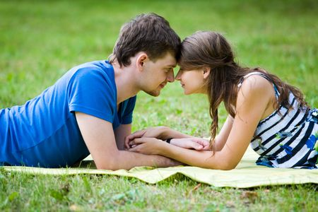 Photo of pretty girl and handsome guy lying on green grass in front of each other and touching one another's face and hands Stock Photo - 3452569