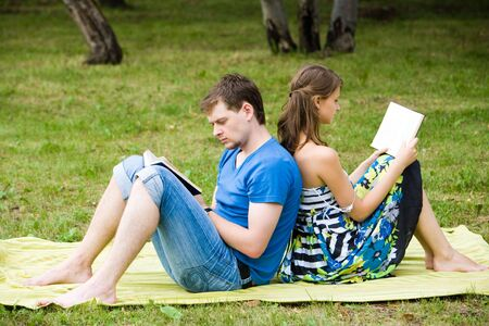 Image of young students sitting aback to each other and reading books in the countryside Stock Photo - 3452377