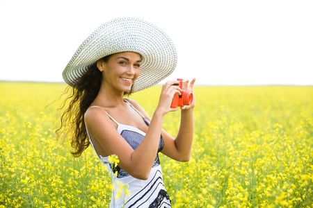 Photo of young woman wearing hat holding photo camera on meadow in summer photo