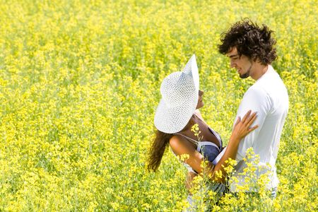Photo of happy couple embracing on meadow of yellow flowers at summertime photo