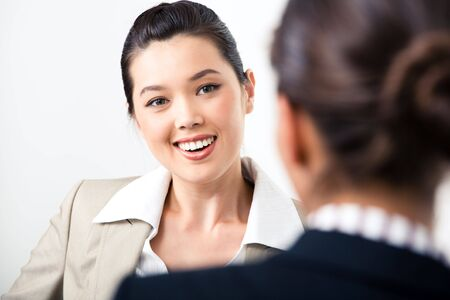 Portrait of confident business lady looking at partner and speaking to her  Stock Photo