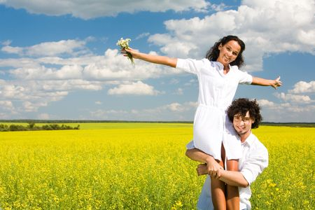 Portrait of young man holding his happy girlfriend on hands  photo
