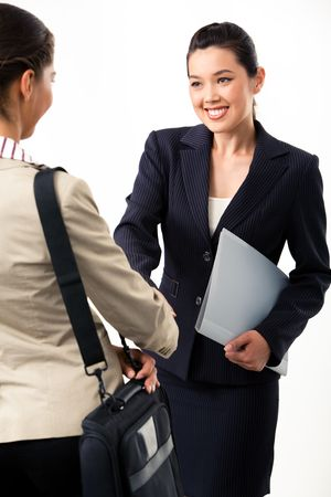Portrait of two businesswomen shaking hands at meeting each other and smiling photo