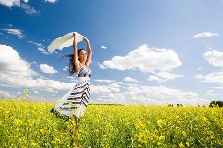 donne eleganti: Felice immagine di donna in possesso di un tessuto bianco nel prato giallo