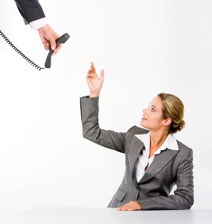 Image of serious receptionist raising hand for receiver while looking aside over white background photo
