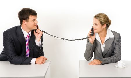talk to the hand: Portrait of business partners speaking on the telephone and looking at each other with smiles Stock Photo
