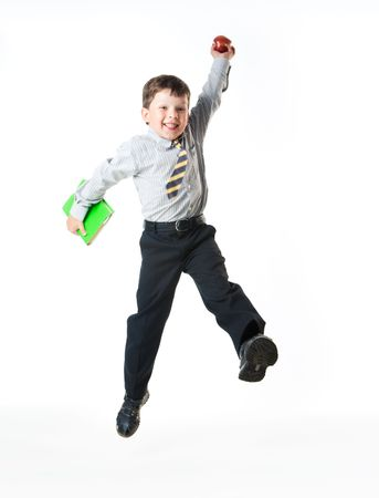 excited people: Portrait of schoolboy with apple and book jumping in the studio Stock Photo