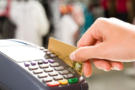 business transaction: Close-up of human hand holding plastic card in payment machine Stock Photo