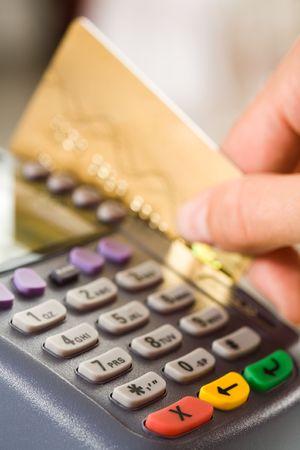 thumb keys: Close-up de la m�quina de botones de pago con la celebraci�n de la mano del hombre cerca de la tarjeta de pl�stico