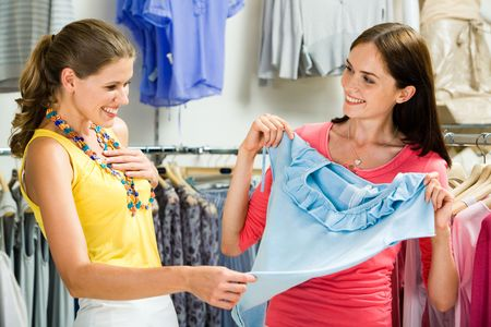 tanktop: Image of surprised girl looking at blue tanktop in her friend�s hands in the department store