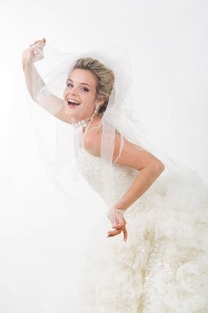 Photo of happy bride looking out of her veil and laughing at camera Stock Photo - 3516083