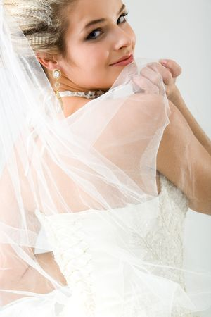 marriageable: Beautiful bride staring over shoulder at camera holding veil