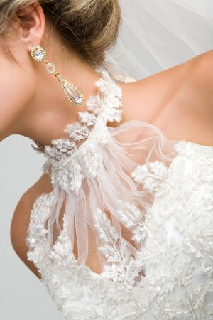 Close-up of bridal neck and chest framed by white wedlock lace and with elegant earring in ear photo
