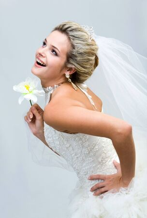 looking upwards: Portrait of joyful bride holding flower in hand and laughing while looking upwards