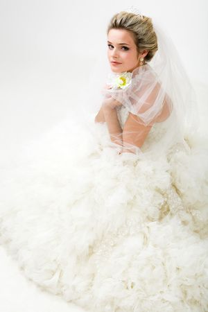 Foto von eleganten Braut in modischen Ehe mit Blume in der Hand sitzen und sich mit Kamera