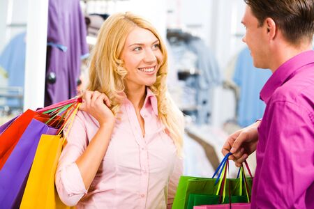 Portrait of happy blond woman looking at smiling man and holding bags in hands photo
