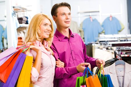 shoppingbag: Portrait of modern couple with shopping bags looking at clothes in the trade center Stock Photo