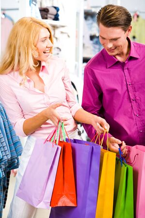 Portrait of cheerful woman showing presents to her boyfriend in the store photo