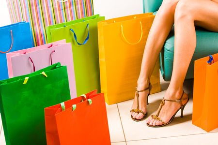 shoppingbag: Image of feminine slim legs wearing fashionable sandals with a lot of bags around Stock Photo