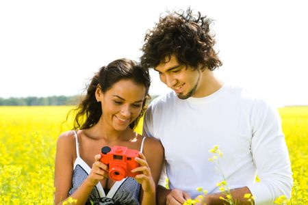 Portrait of happy guy looking at photo camera in girl�s hands standing near by photo