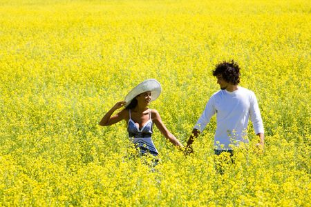 Image of amorous couple walking in yellow meadow holding by hands and looking at each other photo